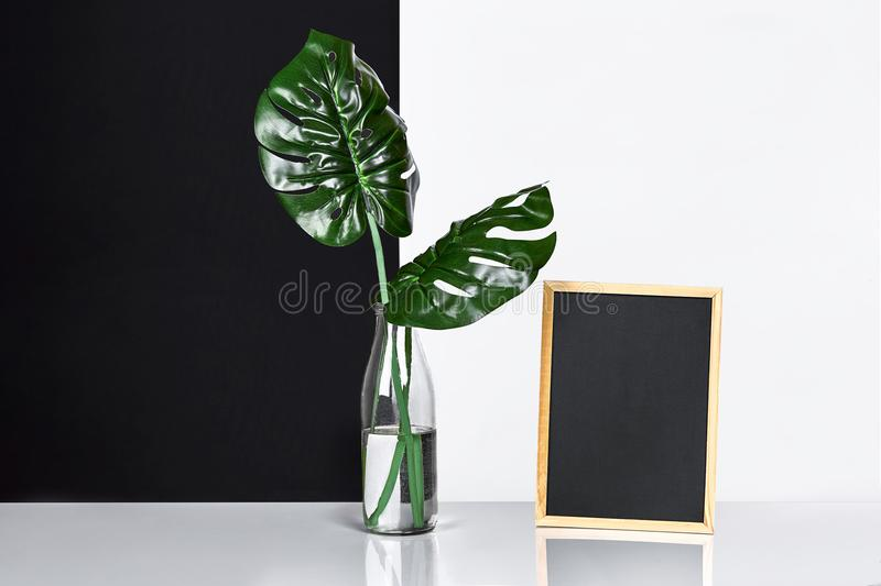 The stylish interior with mock up poster frame, leaves in glass bottle on table with black and white wall on background. stock photography