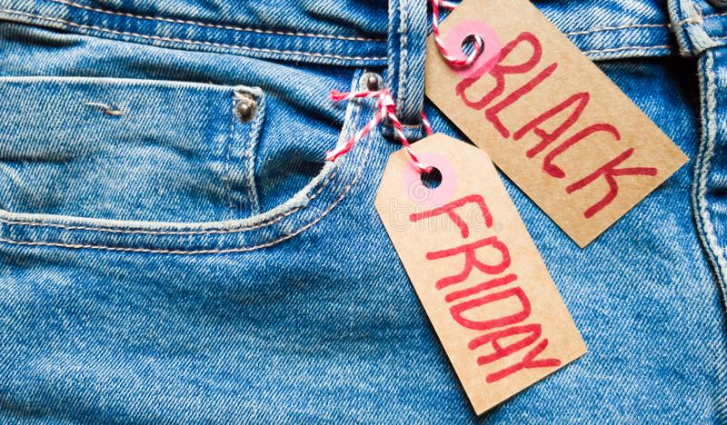 Stylish jeans with a black friday flag. Black friday and cyber monday sale discount concept tag with blue jeans. Black friday stock photography