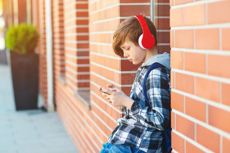 Stylish kid boy with headphones using phone at city street. Young boy plays online game at smartphone. Preteen boy listens to the royalty free stock photo