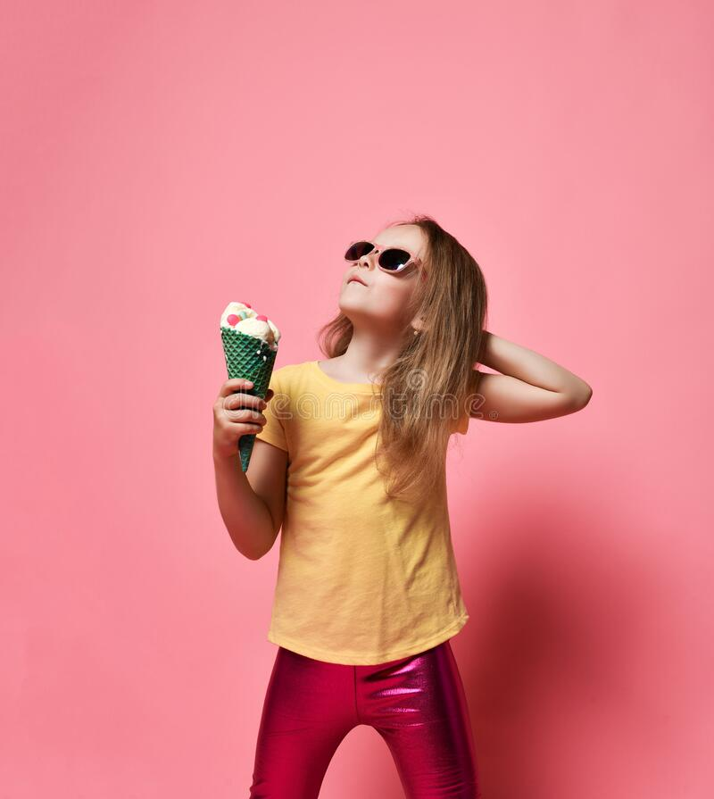 Free Stylish Kid Girl In T-shirt And Leggings Stands With Big Vanilla Ice Cream With Candies In Waffles Cone And Looks Up Royalty Free Stock Photography - 193264717