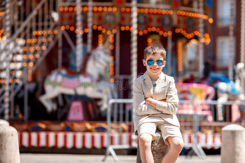 Stylish kid in a nice suit and glasses near the traditional French merry-go-round. Beauvais, France stock photos