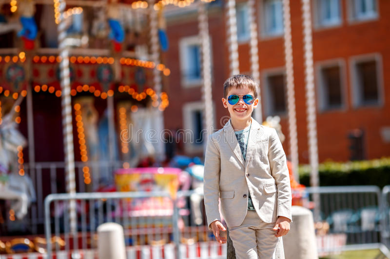 Stylish kid in a nice suit and glasses near the traditional French merry-go-round. Beauvais, France stock image