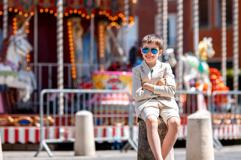 Stylish kid in a nice suit and glasses near the traditional French merry-go-round. Beauvais, France stock photography