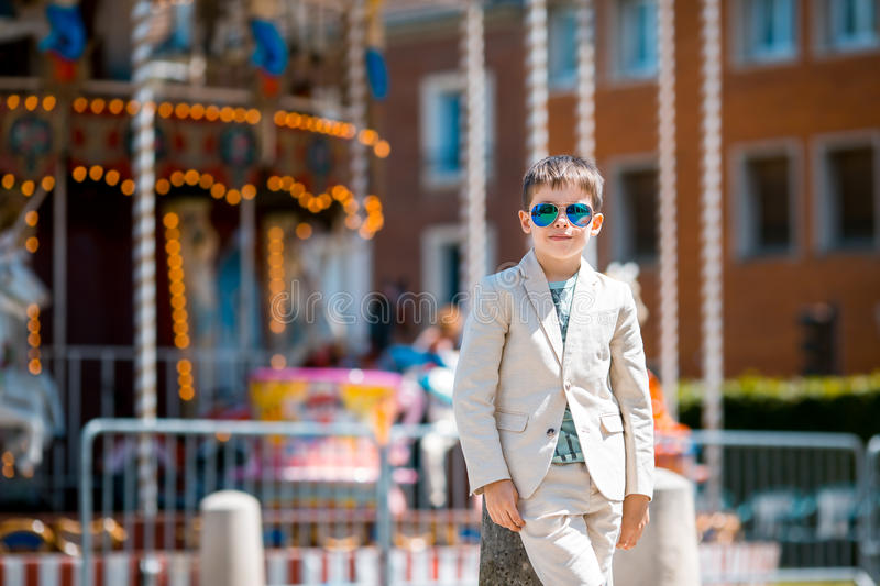 Stylish kid in a nice suit near the traditional. Stylish kid in a nice suit and glasses near the traditional French merry-go-round, Beauvais, France royalty free stock photos