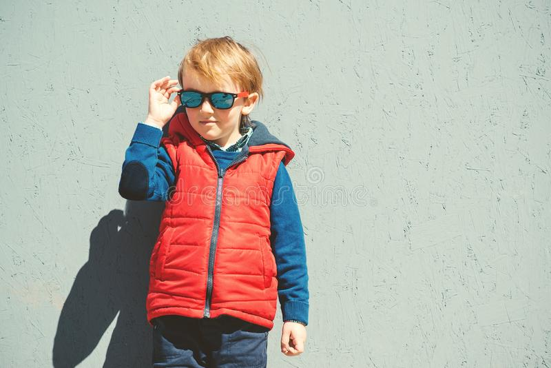 Stylish kid in trendy sunglasses. Kids fashion. Cute little blondy boy in red jacket standing over grey wall outdoors in sunny day stock photo
