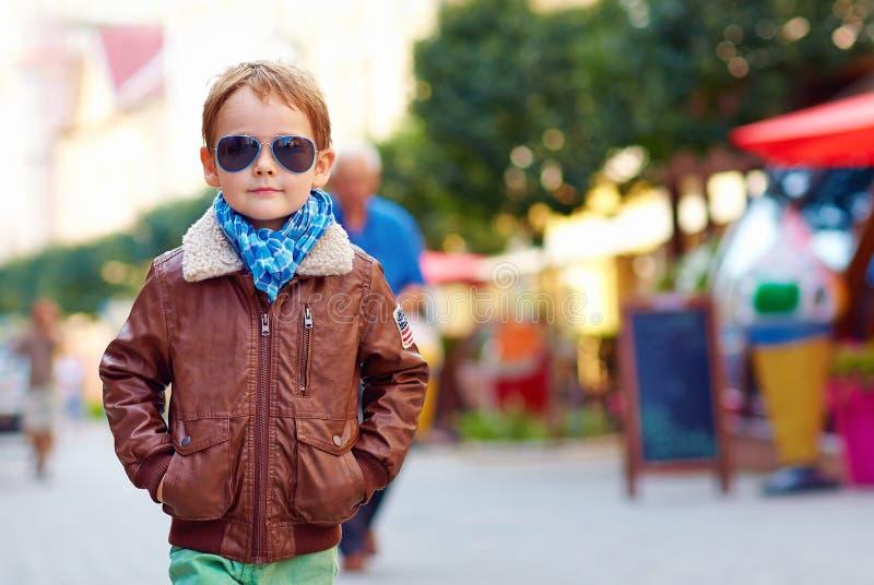 Stylish kid walking city street, autumn fashion royalty free stock photography
