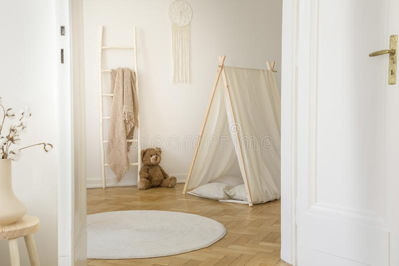 Stylish kids playroom with copy space. Stylish kids playroom with white tent, teddy bear, macrame on the wall and round carpet on the parquet, real photo with stock image