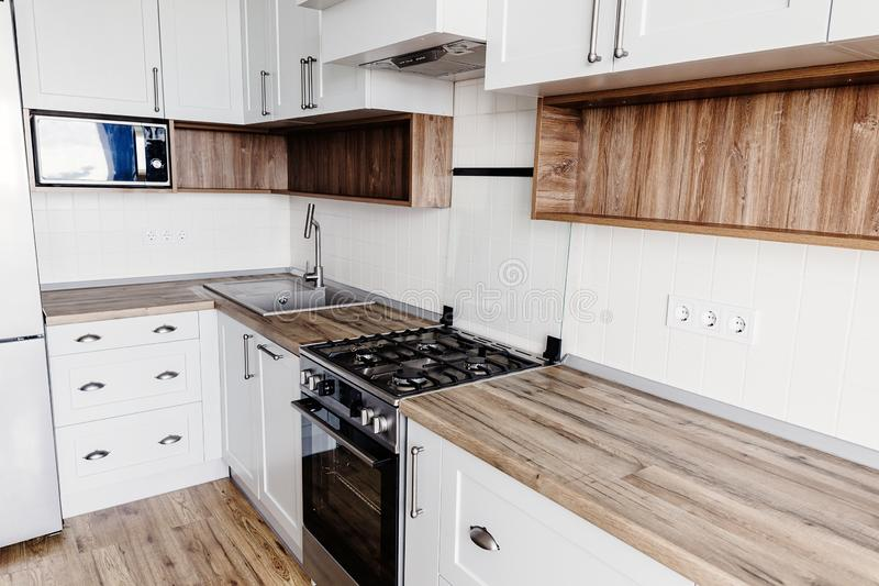 Stylish kitchen interior design. Luxury modern kitchen furniture in grey color and steel oven,fridge, sink, wooden tabletop. Gray. Cabinets in scandinavian stock images