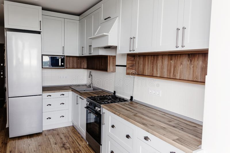 Stylish kitchen interior design. Luxury modern kitchen furniture in grey color and steel oven,fridge, sink, wooden tabletop. Gray. Cabinets in scandinavian royalty free stock photo