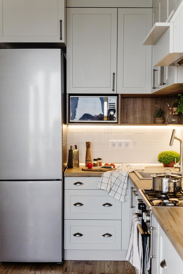 Stylish kitchen interior design. Luxury modern kitchen furniture in grey color and steel oven,fridge, sink, wooden tabletop, pots. Gray cabinets in stock photo