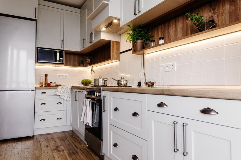 Stylish kitchen interior design. Luxury modern kitchen furniture in grey color and steel oven,fridge, sink, wooden tabletop, pots. Gray cabinets in stock images