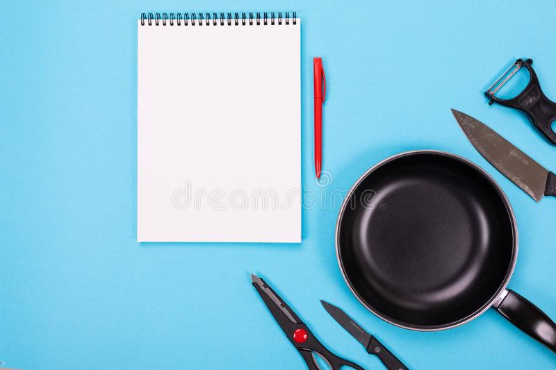 Kitchen utensils and clean sheet of paper isolated on blue background. Stylish kitchen tools and a clean white sheet of paper in between isolated close-up on a stock image