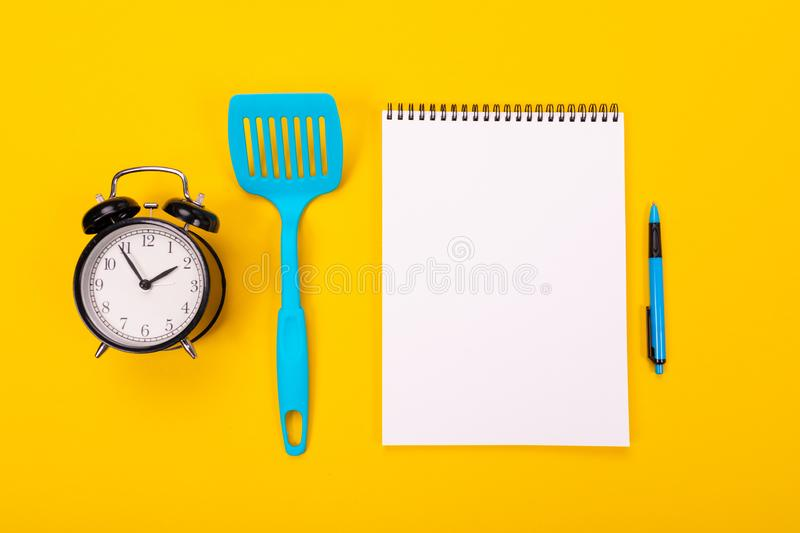 Kitchen utensils and clean sheet of paper isolated on yellow background. Stylish kitchen tools and a clean white sheet of paper in between isolated close-up on a royalty free stock photo