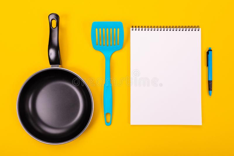 Kitchen utensils and clean sheet of paper isolated on yellow background. Stylish kitchen tools and a clean white sheet of paper in between isolated close-up on a royalty free stock photography