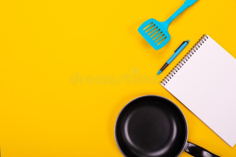Kitchen utensils and clean sheet of paper isolated on yellow background. Stylish kitchen tools and a clean white sheet of paper in between isolated close-up on a stock image