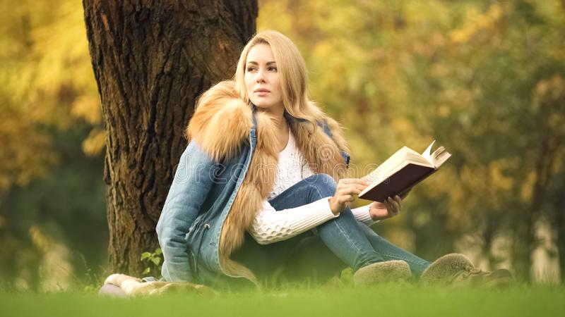 Stylish lady reading adventure book and enjoying autumn weather in central park stock photography