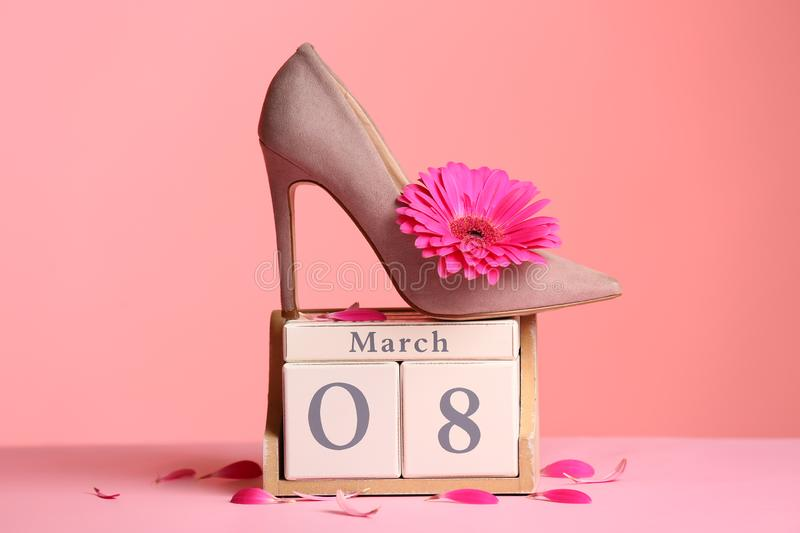 Stylish lady`s shoe, flower and wooden block calendar on table against color background. stock image