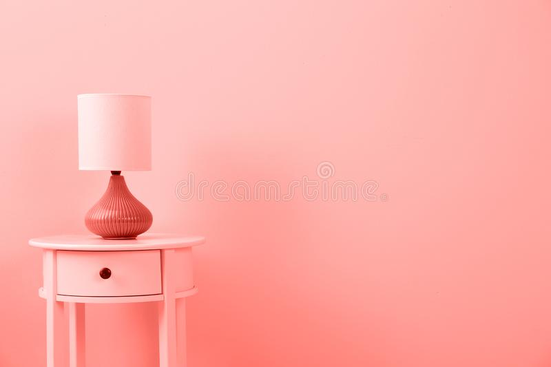 Stylish lamp on table against color wall, space for text. Design with living coral color stock images