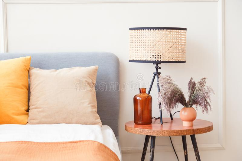 Stylish lamp on wooden nightstand next to flower in big glass vase in scandinavian bedroom interior royalty free stock image