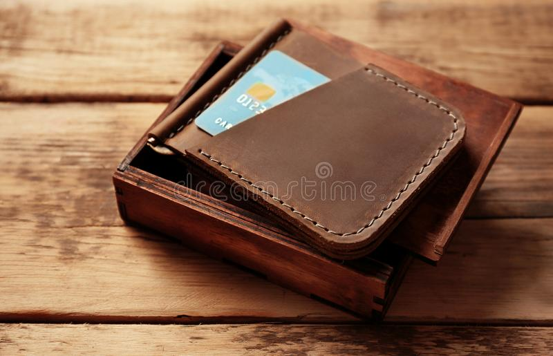 Stylish leather wallet with credit card and box. On wooden background royalty free stock image