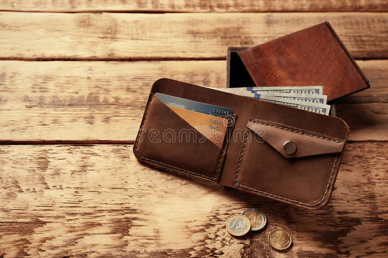Stylish leather wallet with money and box. On wooden background royalty free stock photo