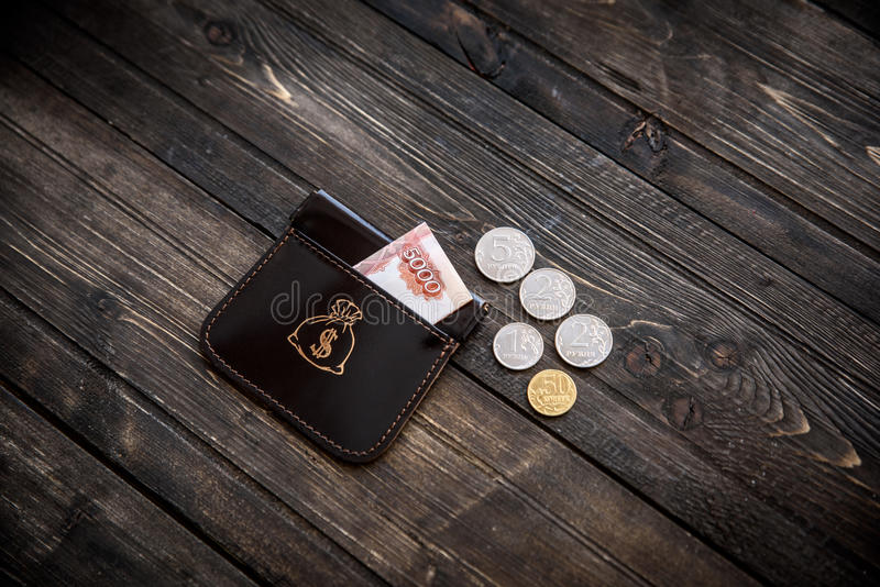 Stylish leather wallet with money and box on wooden background.  royalty free stock photo