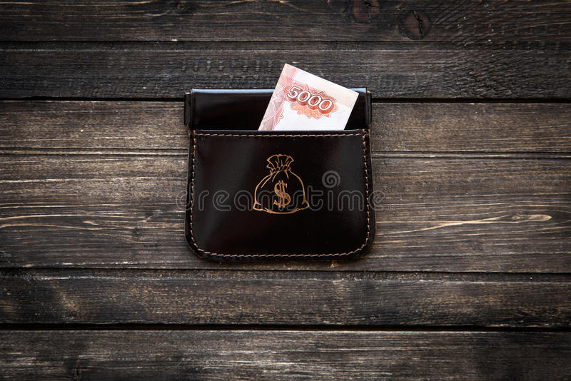 Stylish leather wallet with money and box on wooden background.  royalty free stock photos