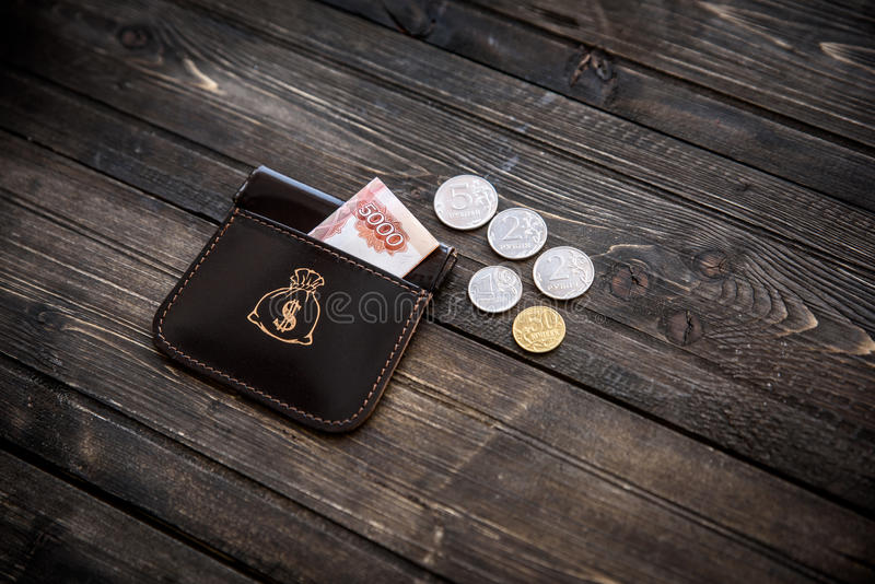 Stylish leather wallet with money and box on wooden background.  royalty free stock image