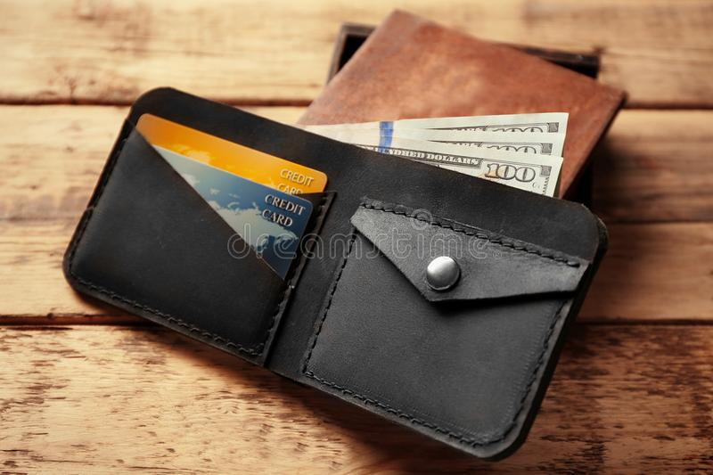 Stylish leather wallet with money and box. On wooden background stock photography
