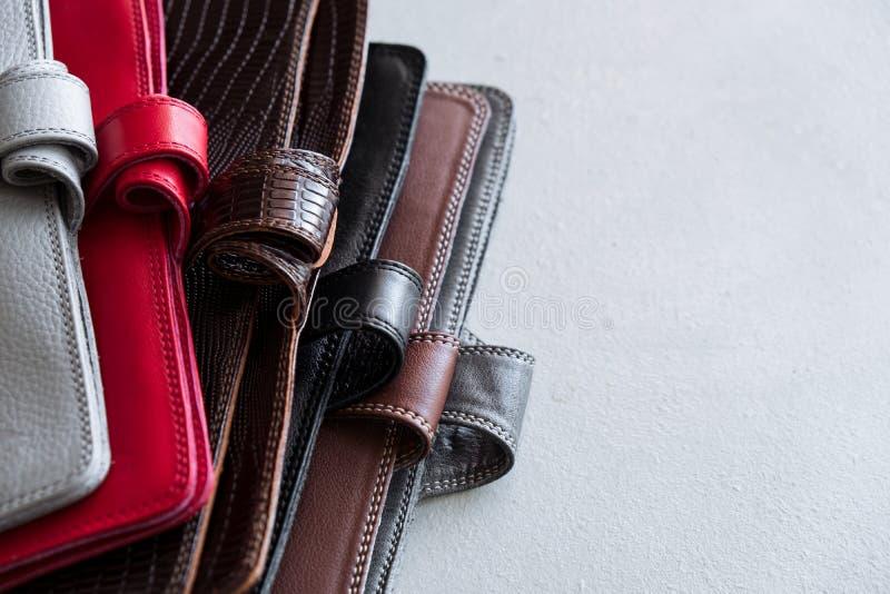 Stylish leather wallets on grey background. Stylish leather wallets in box on wooden background royalty free stock photo