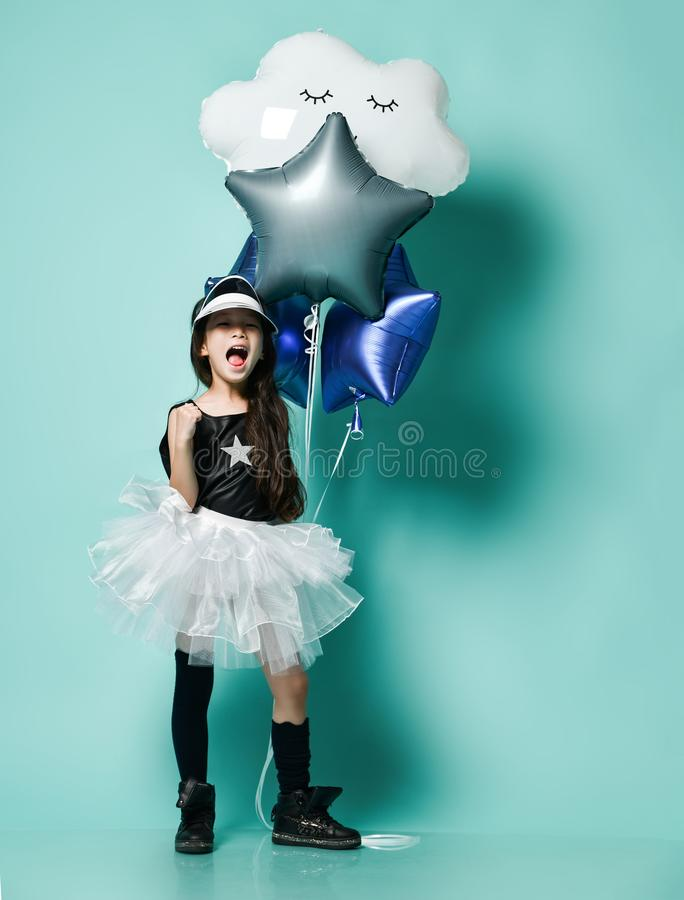 Cute little asian girl kid in fashion skirt holds metallic balloons for kids birthday and screams shouts sings on blue mint. Stylish little asian girl kid in royalty free stock image