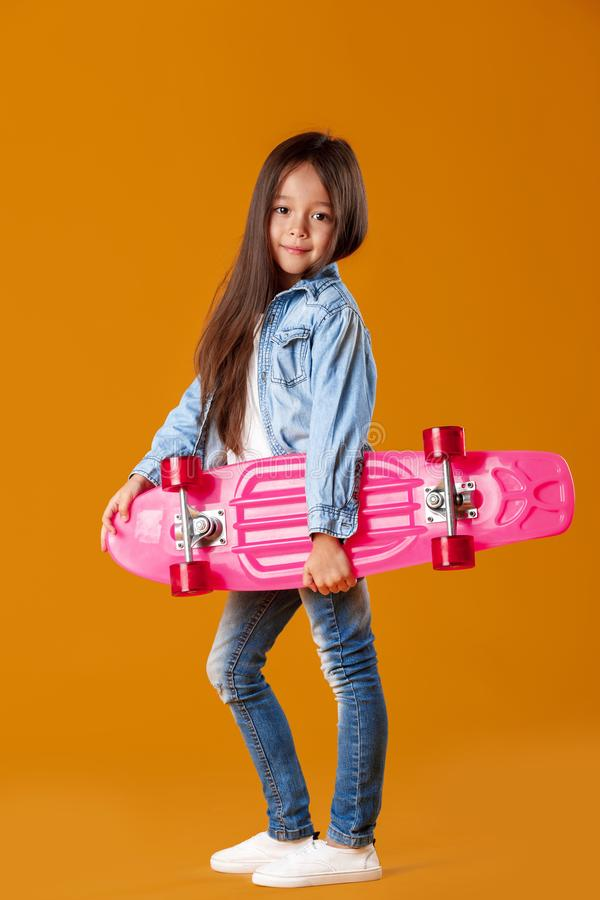 Stylish little child girl with skateboard in denim on orange background royalty free stock image