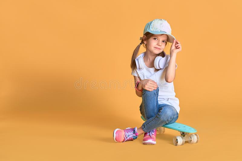 Stylish little girl child girl in casual with skateboard over yellow background.  stock photography
