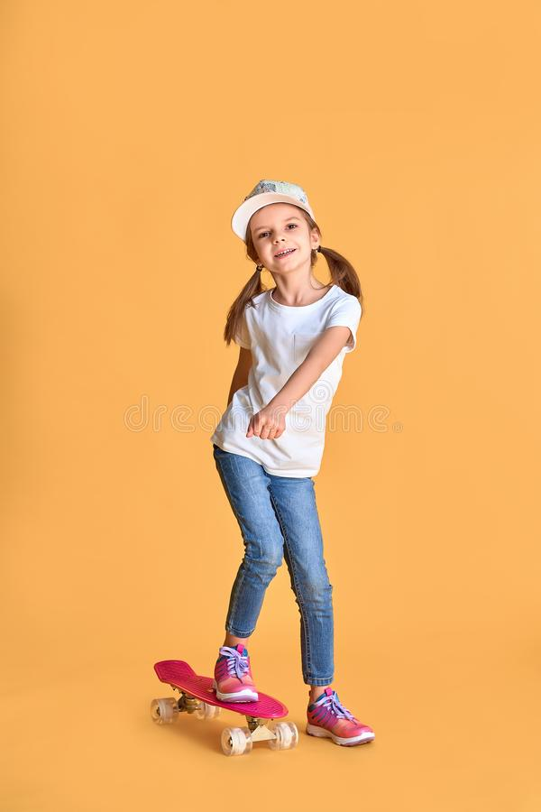 Stylish little girl child girl in casual with skateboard over yellow background.  stock photo