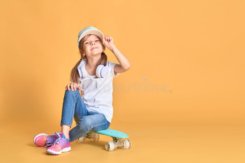 Stylish little girl child girl in casual with skateboard over yellow background.  royalty free stock photos