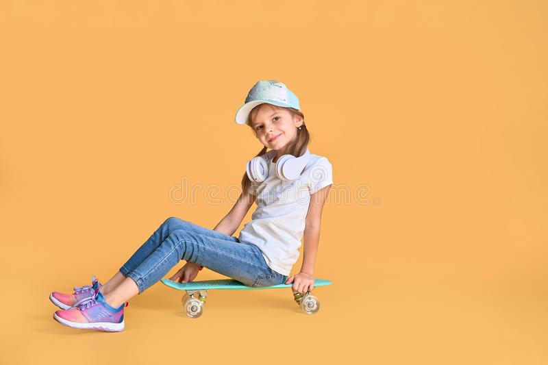 Stylish little girl child girl in casual with skateboard over yellow background.  royalty free stock images