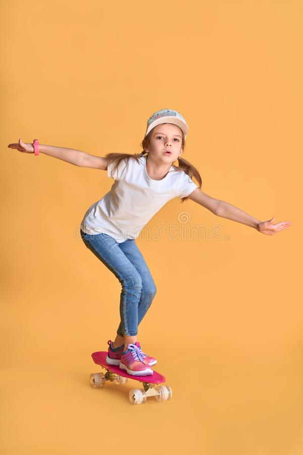 Stylish little girl child girl in casual with skateboard over yellow background.  royalty free stock photography
