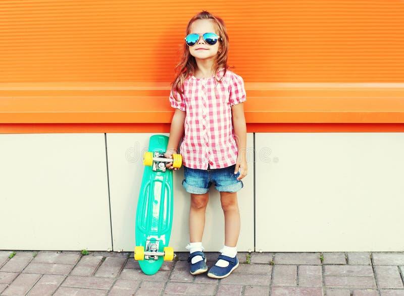 Stylish little girl child with skateboard wearing sunglasses and checkered shirt over orange background stock image