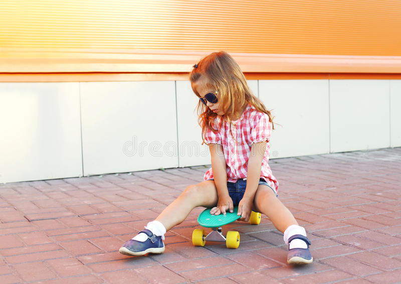 Stylish little girl child with skateboard wearing sunglasses in city. Stylish little girl child with skateboard wearing a sunglasses in city royalty free stock image