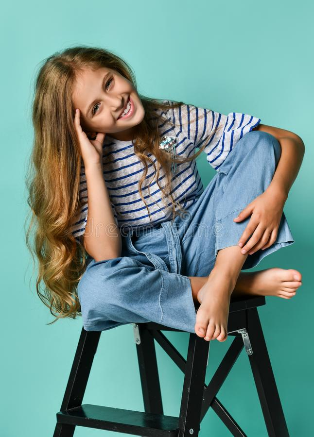 Stylish little girl child wearing summer or autumn jeans clothes sitting on a high chair in the studio. stock images
