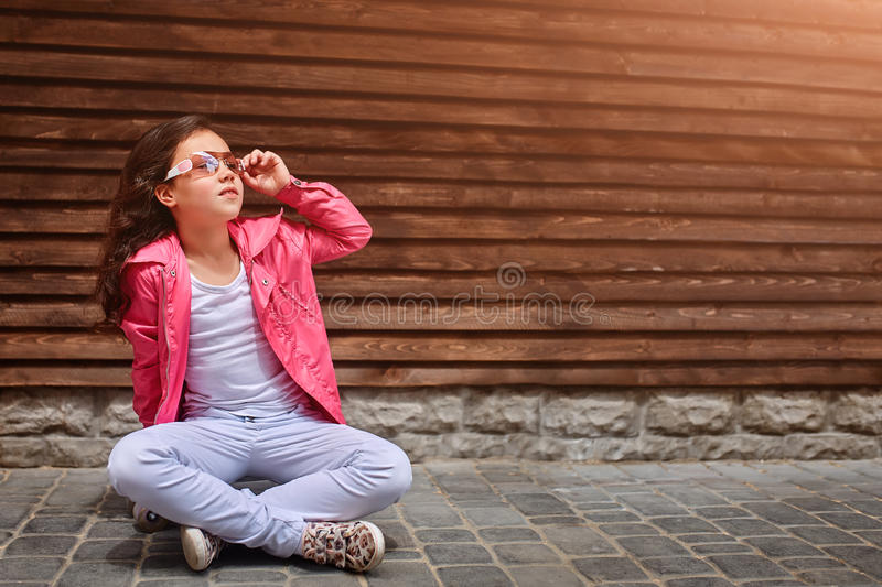 Stylish little girl child wearing a summer or autumn pink jacket, white jeans, sunglasses stock photos