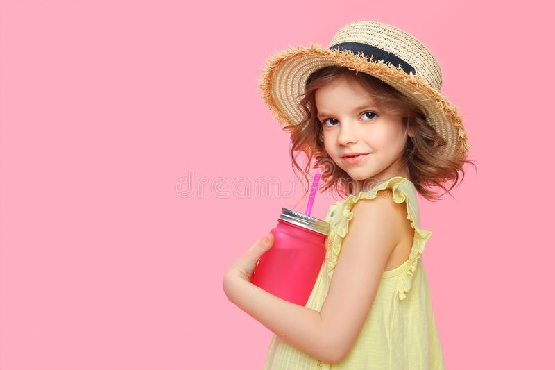 Stylish little girl with drink on pink. Side view of pretty little model in straw hat and summer dress holding glass with refreshing lemonade stock image