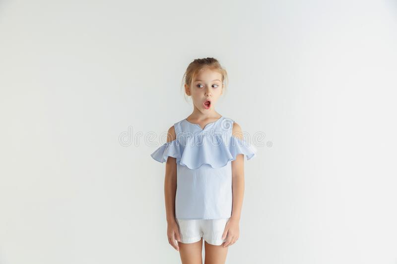 Little smiling girl posing in casual clothes on white studio background. Stylish little smiling girl posing in casual clothes isolated on white background royalty free stock image
