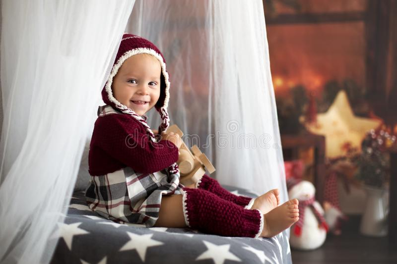 Stylish little toddler boy, playing around christmas decoration. At home stock photo