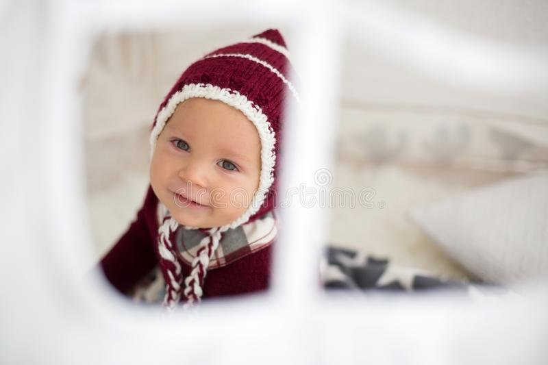 Stylish little toddler boy, playing around christmas decoration. At home royalty free stock image