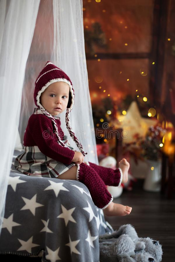 Stylish little toddler boy, playing around christmas decoration. At home royalty free stock photos