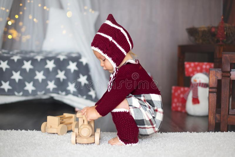 Stylish little toddler boy, playing around christmas decoration. At home stock images