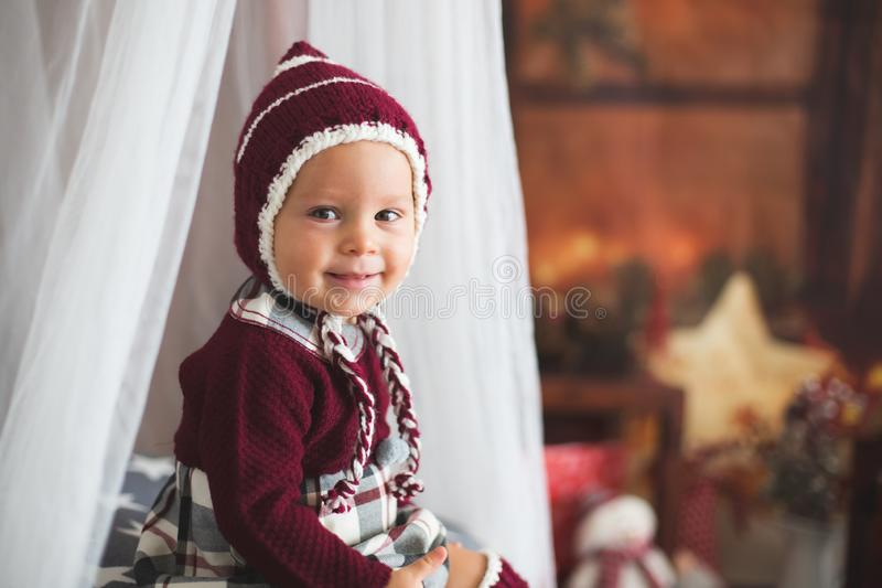 Stylish little toddler boy, playing around christmas decoration. At home royalty free stock photography