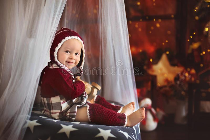 Stylish little toddler boy, playing around christmas decoration. At home royalty free stock images