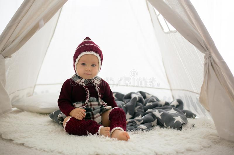 Stylish little toddler boy, playing around christmas decoration. At home stock photography